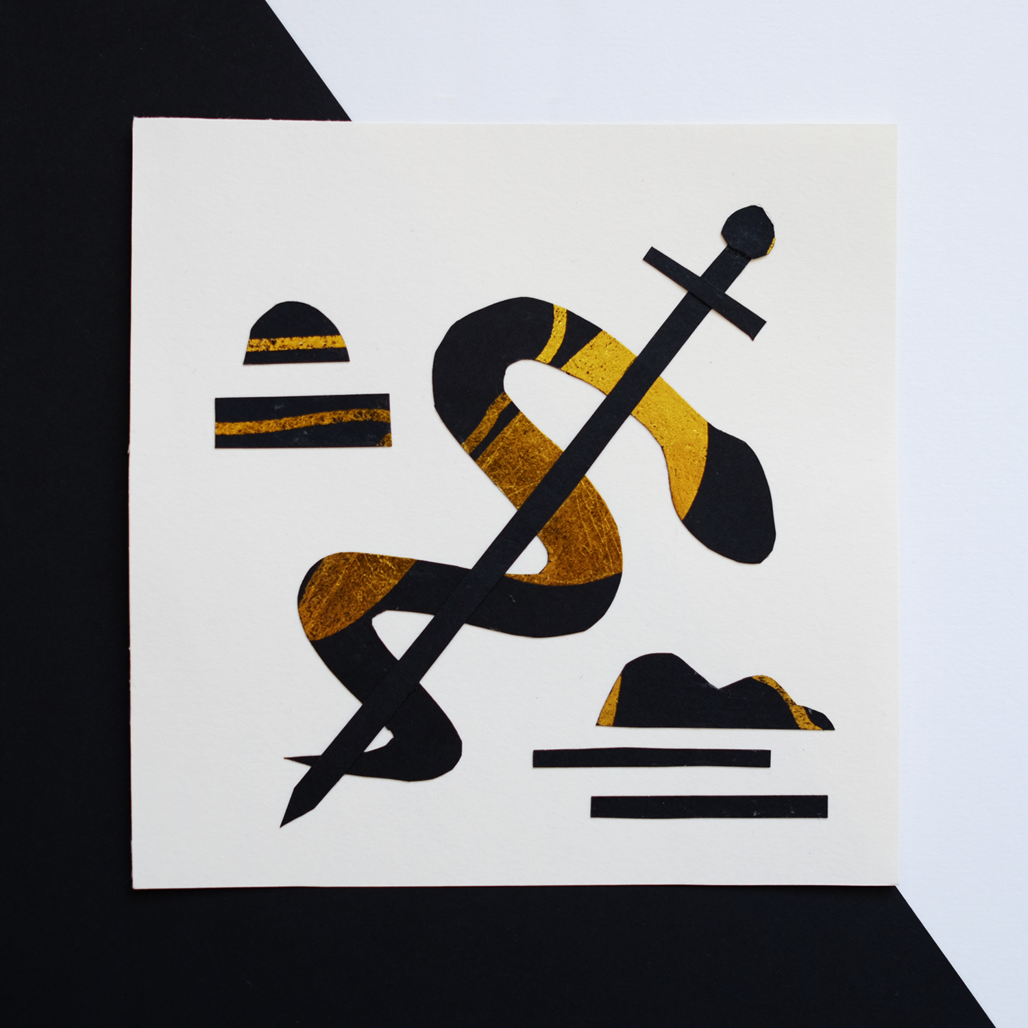 Drawing with scissors, a collage depicting a snake and sword made out of black paper covered with gold foil by Monsie Monika Jurczyk